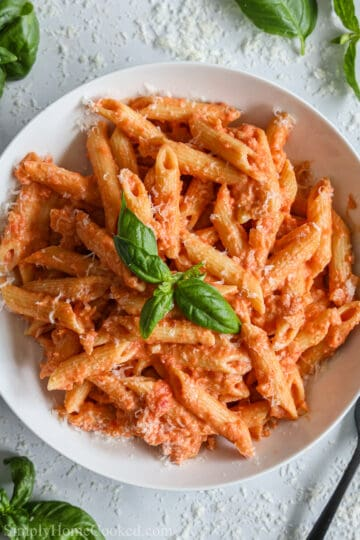 overhead image of penne alla vodka in a white plate with basil and grated parmesan cheese on top
