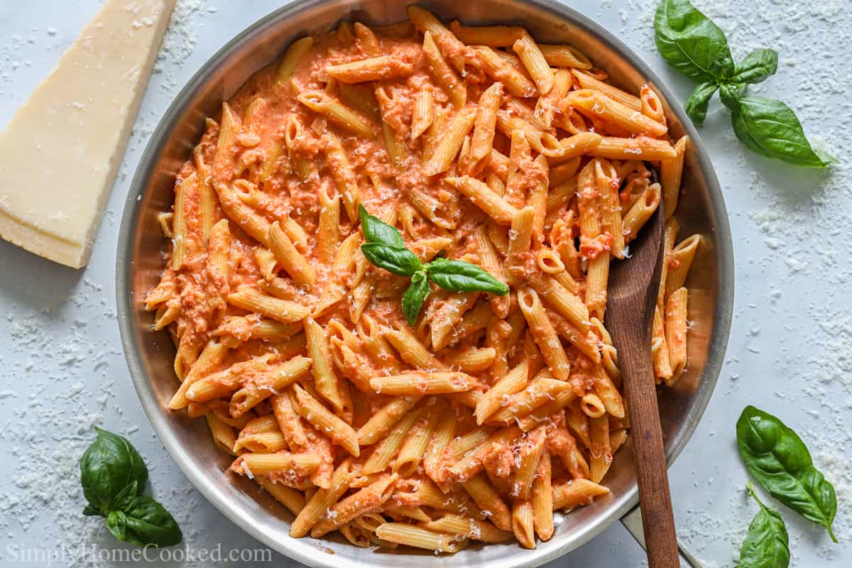 overhead image of penne alla vodka pasta in a large stainless steal pan with a wooden spoon inside
