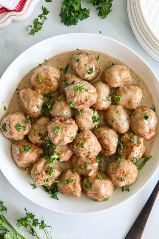 Overview of a white bowl filled with Perfect Swedish Meatballs sprinkled with parsley.