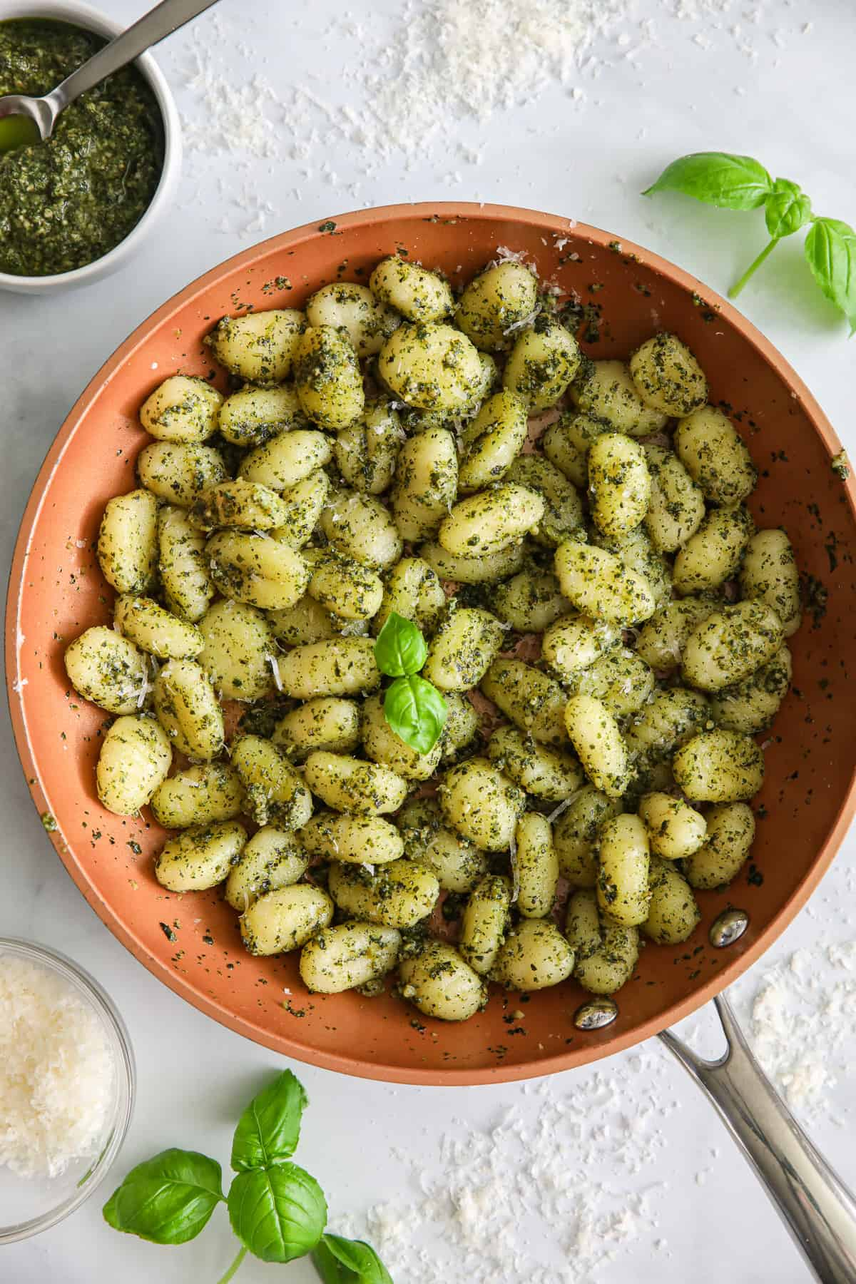 Pan of Pesto Gnocchi with basil, Parmesan cheese, and a bowl of basil pesto on the side.