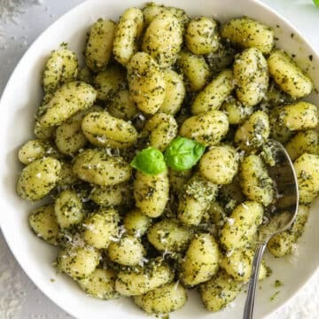 A bowl of Pest Gnocchi with a spoon, and basil, Parmesan cheese, and basil pesto on the side.
