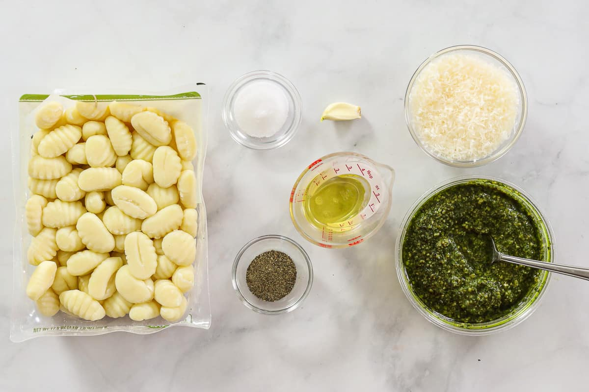 Ingredients for Pesto Gnocchi, including uncooked gnocchi, Parmesan cheese, basil pesto, garlic, olive oil, salt, and pepper on a white background.