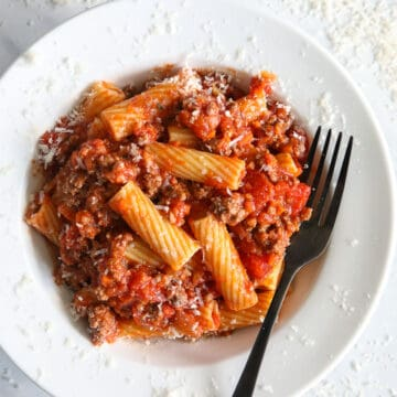 Plate of Rigatoni Bolognese with a fork and grated Parmesan cheese.