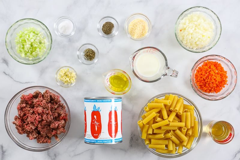 Ingredients for Rigatoni Bolognese including ground beef, rigatoni, tomatoes, onion, garlic, celery, carrot, milk, white wine, olive oil, Parmesan cheese, salt, pepper, and oregano, on a white background.