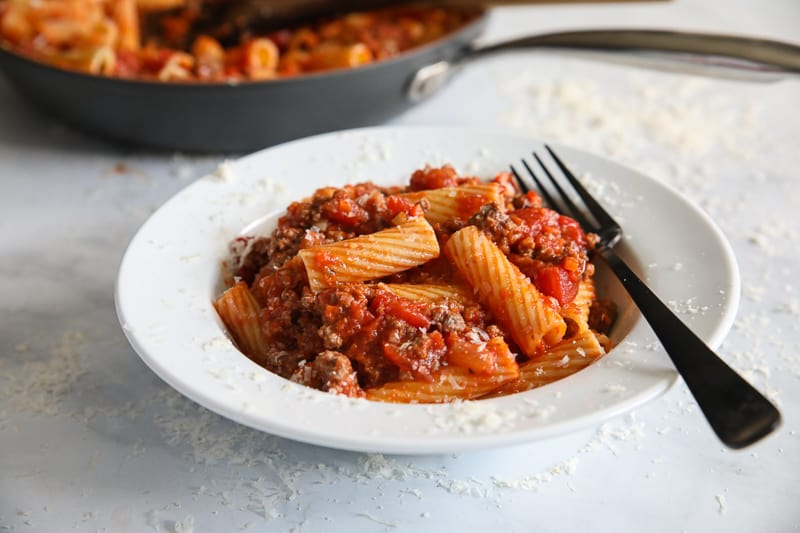 Side view of Rigatoni Bolognese on a plate with a fork, a skillet in the background.