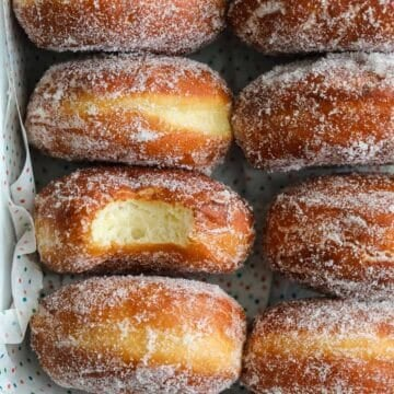 Pan full of Perfect Sugar Donuts, with one in the middle missing a bite.