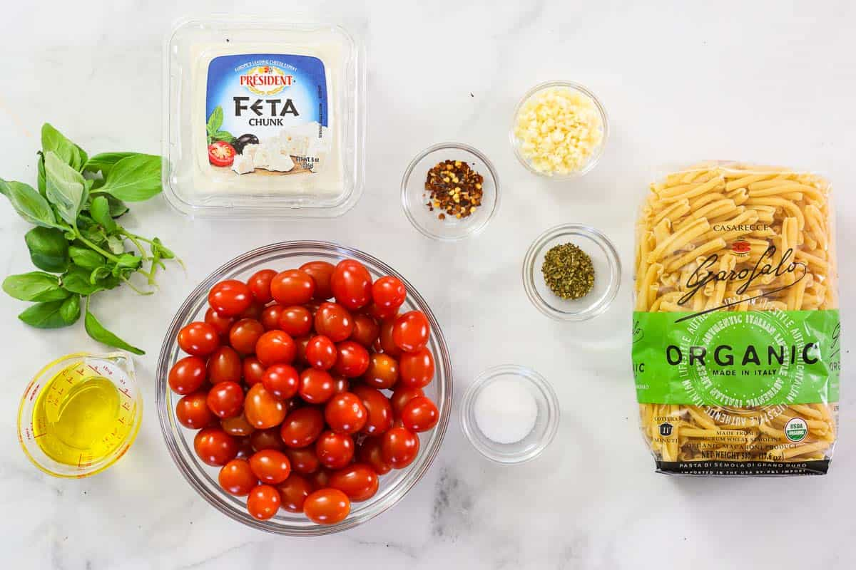 Ingredients for Baked Feta Pasta, including dry pasta, feta cheese, cherry tomatoes, basil leaves, olive oil, salt, pepper, garlic, and red pepper flakes.