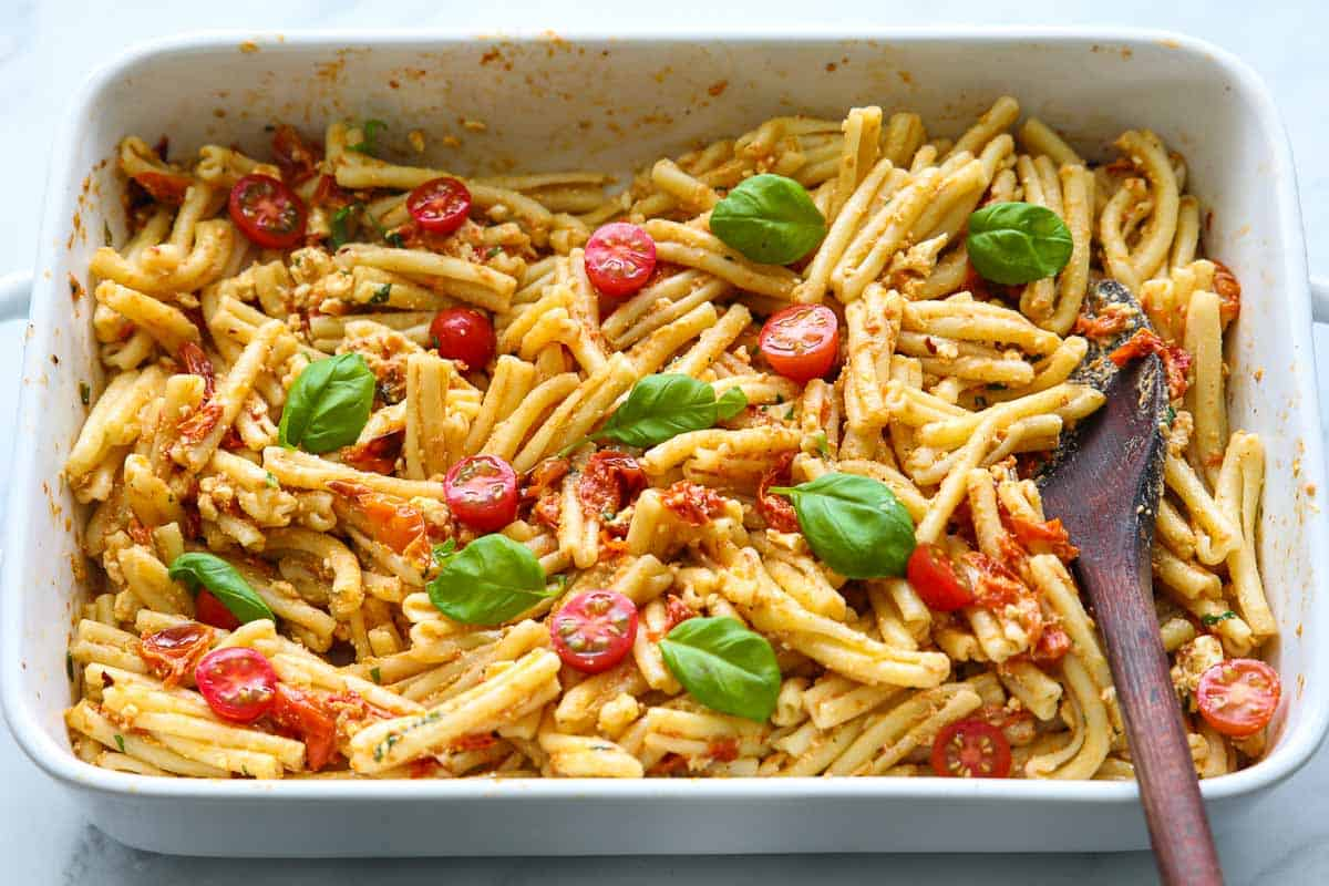 Baking dish with Baked Feta Pasta mixed with a wooden spoon