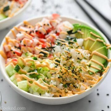 California Sushi Bowl with chopsticks, sushi bowls, and black sesame seeds in the background.