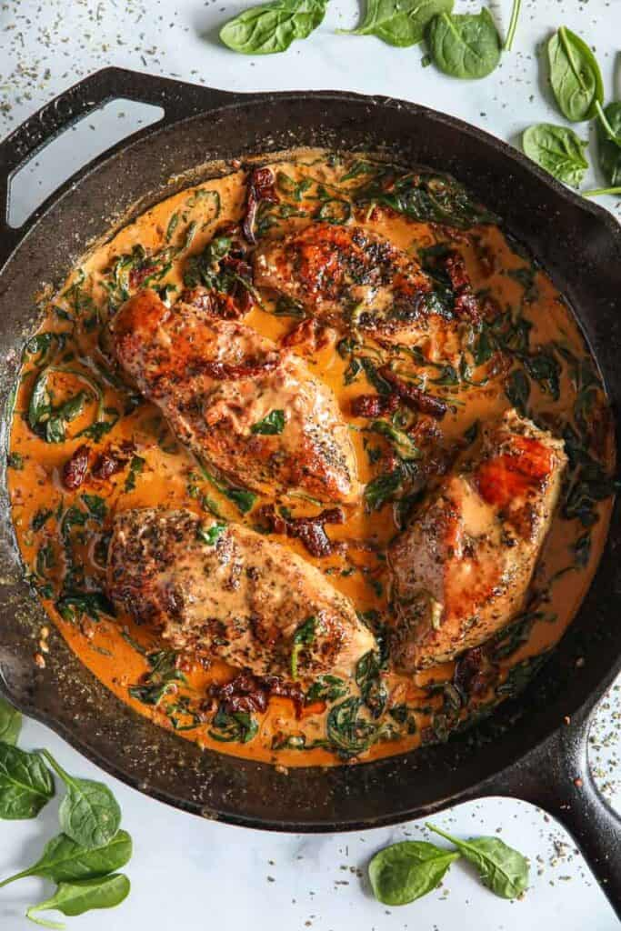 Overhead image of Creamy Tuscan Chicken in a cast iron skillet.