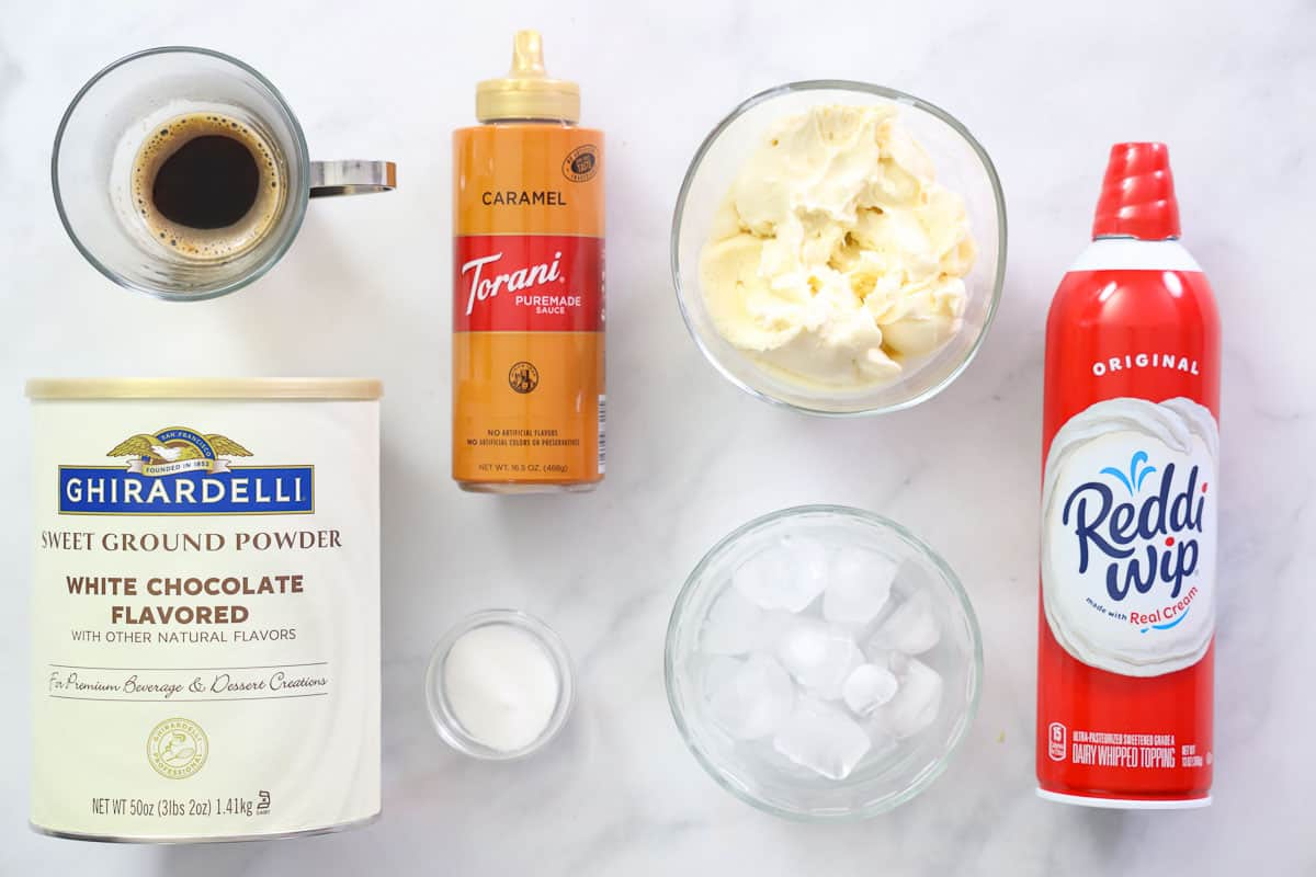Ingredients for Starbucks Caramel Frappuccino copycat recipe, including espresso, white chocolate powder, caramel sauce, vanilla ice cream, sugar, crushed ice, and whipped cream.