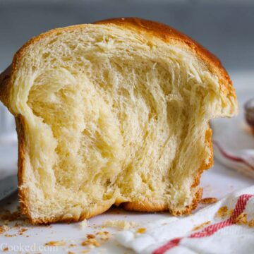 Buttery Brioche Bread with honey and butter in the background.