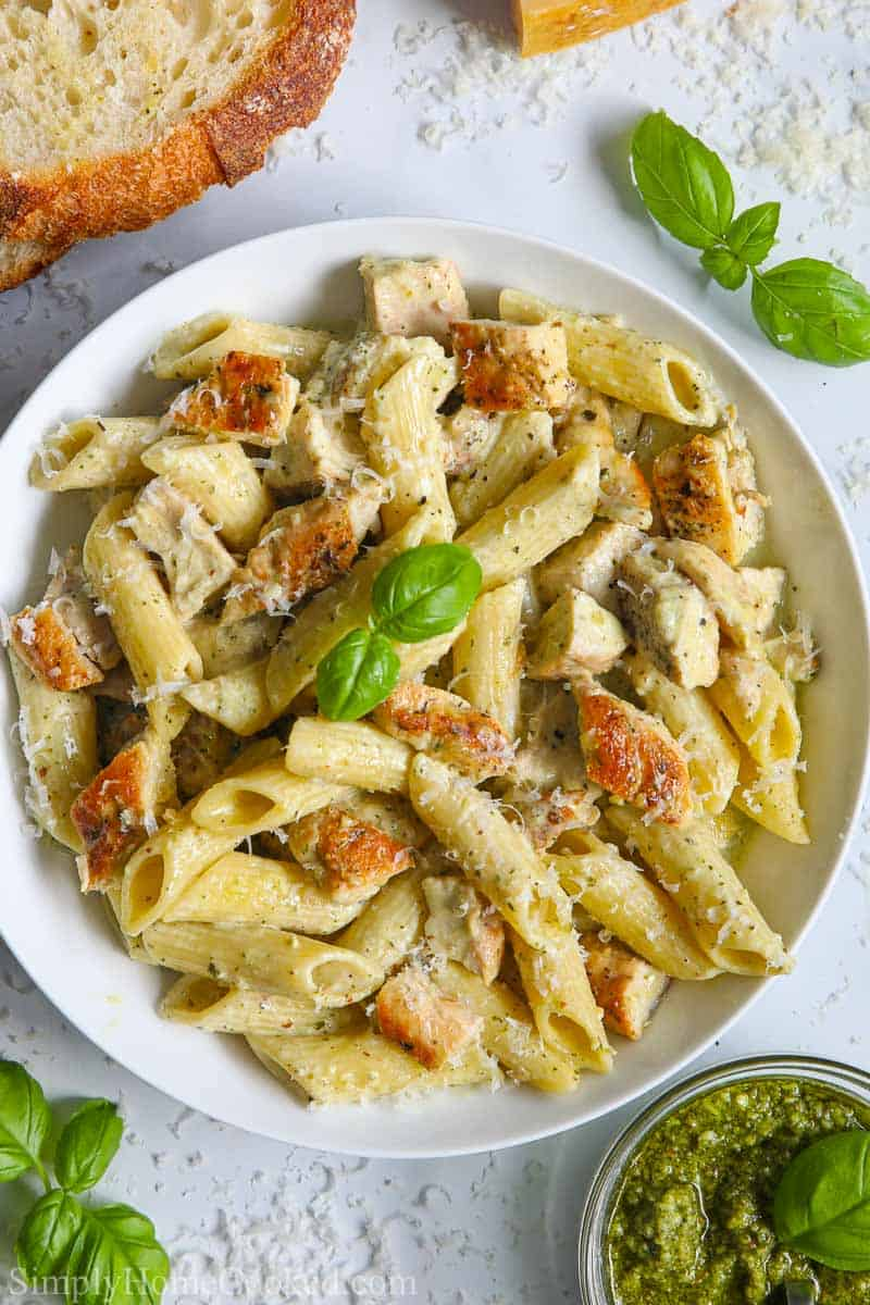 Overview of a plate of Creamy Chicken Pesto Pasta with a sprig of basil garnishing it, and pesto and bread to the side.