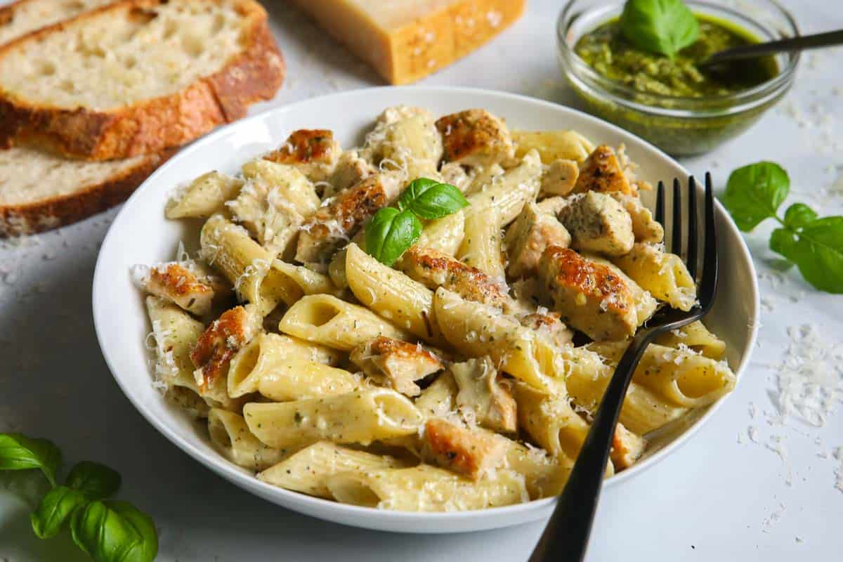 Plate of Creamy Chicken Pesto Pasta with a fork in it and some bread and pesto to the side.