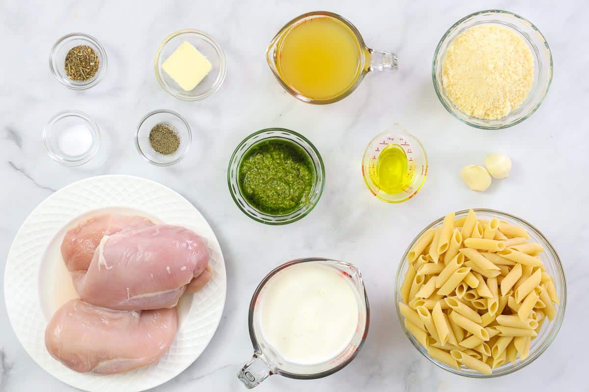 Ingredients for Creamy Chicken Pesto Pasta, including chicken breasts, penne pasta, Parmesan cheese, basil pesto, chicken broth, oil, garlic cloves, salt, pepper, butter, and heavy cream.
