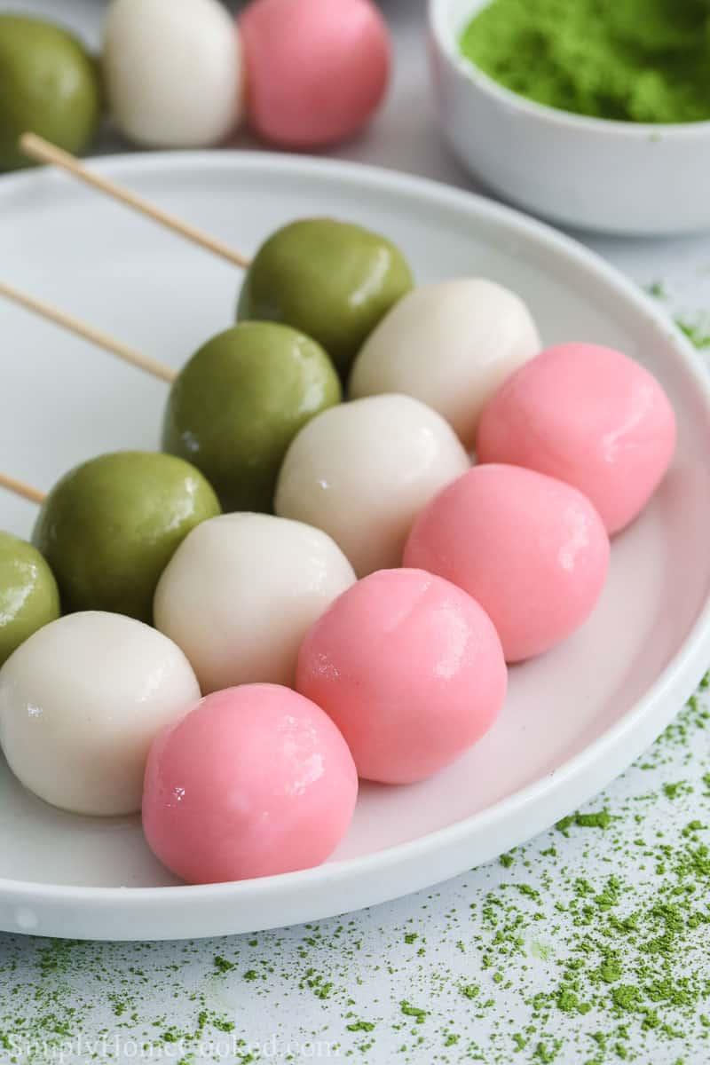 3 Hanami Dango on a white plate with more in the background with matcha powder.