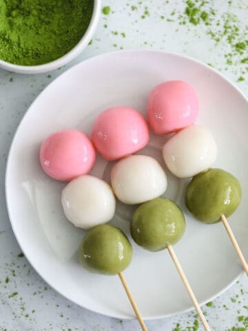 3 Hanami Dango on skewers on a white plate with matcha powder nearby.