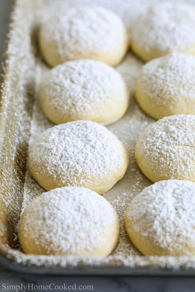 Close up of a tray of Easy Cream Cheese Cookies dusted with powdered sugar