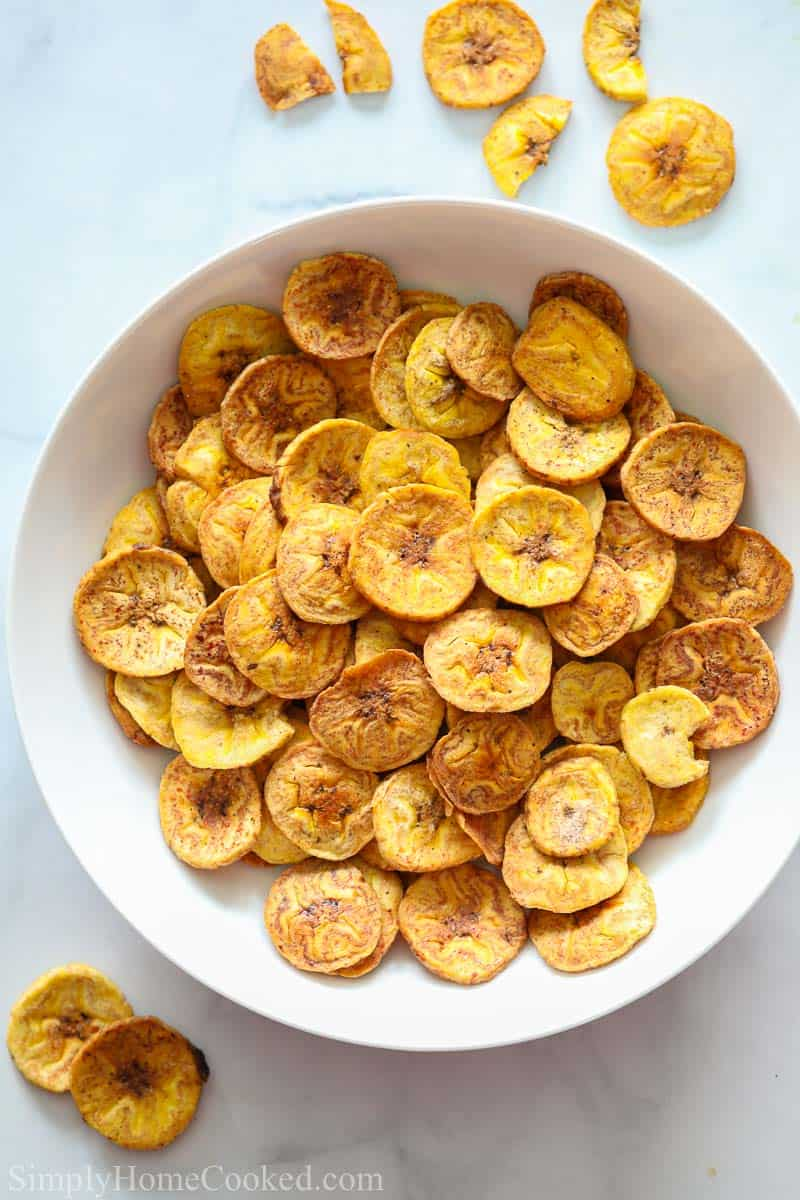 Bowl of Baked Plantain Chips with a few scattered nearby.