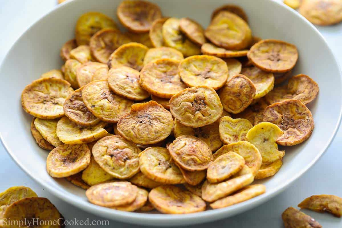 Close up of a bowl of Baked Plantain Chips with a few scattered nearby.