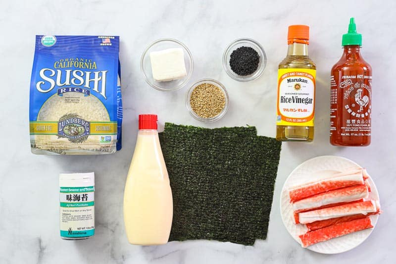 Ingredients for Easy Sushi Bake, including sushi rice, nori sheets, rice vinegar, sriracha, imitation crab, toasted sesame seeds, cream cheese, and mayo on a white background.