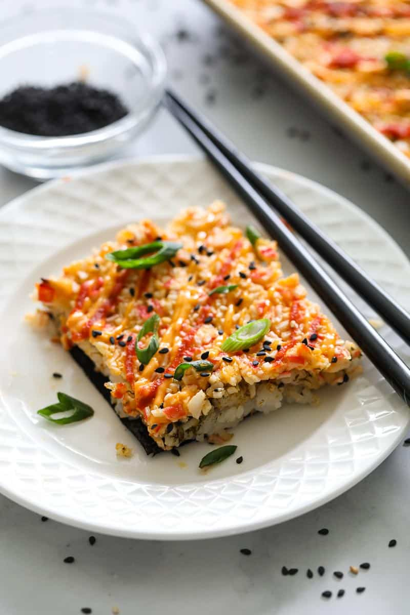 Easy Sushi Bake on a white plate with chopsticks, and a bowl of crumbled nori in the background.