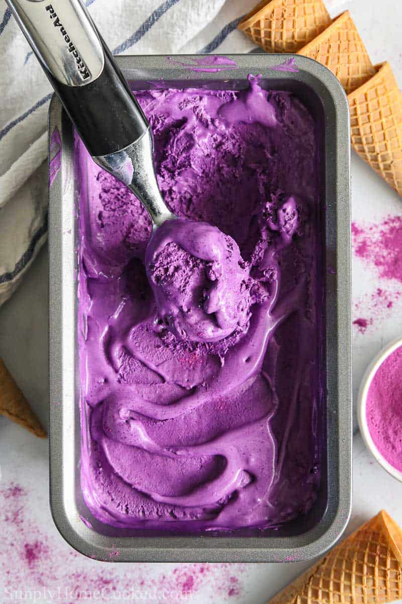 Loaf pan of Easy Ube Ice Cream with an ice cream scooper in the middle, ice cream cones nearby.