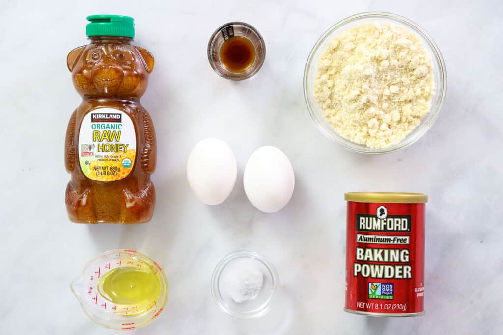 Ingredients for Almond flour pancakes, including honey, blanched almond flour, baking powder, salt, eggs, oil, and vanilla extract.