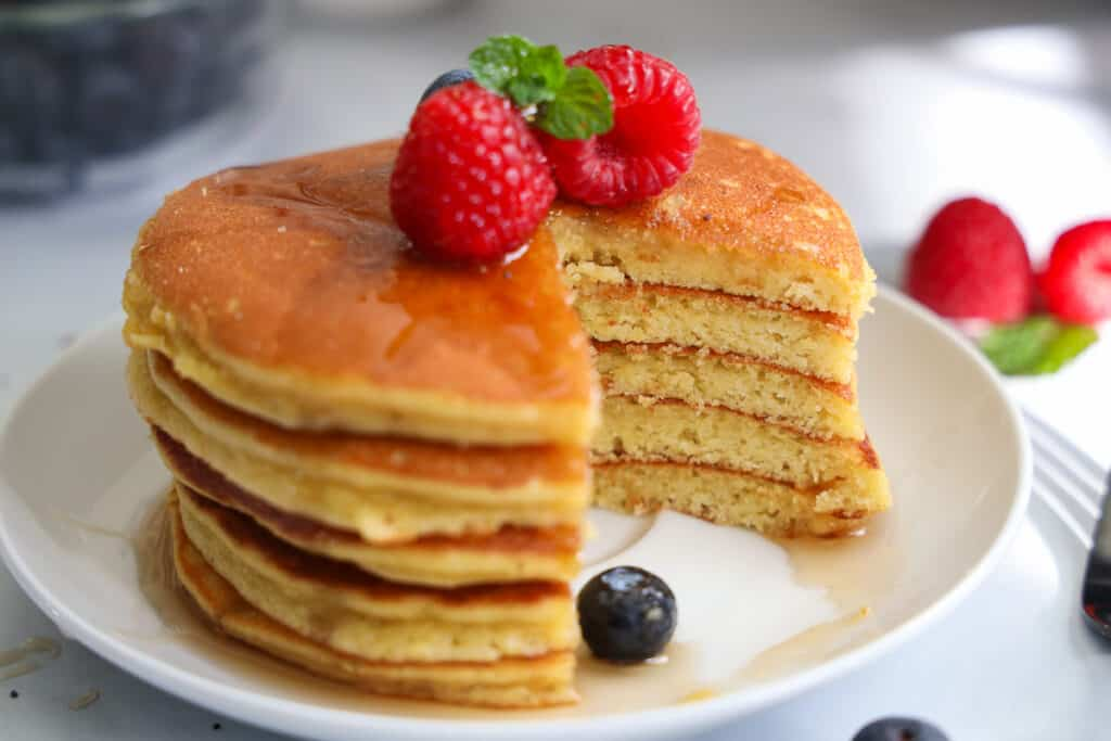 Stack of Almond Flour Pancakes with raspberries, blueberries, and mint on top with syrup, a slice missing.