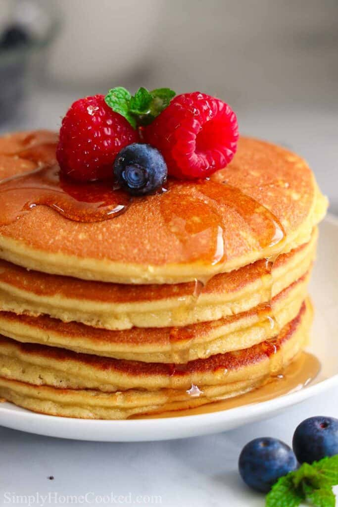 Stack of Almond Flour Pancakes with raspberries, blueberries, and mint on top with syrup.