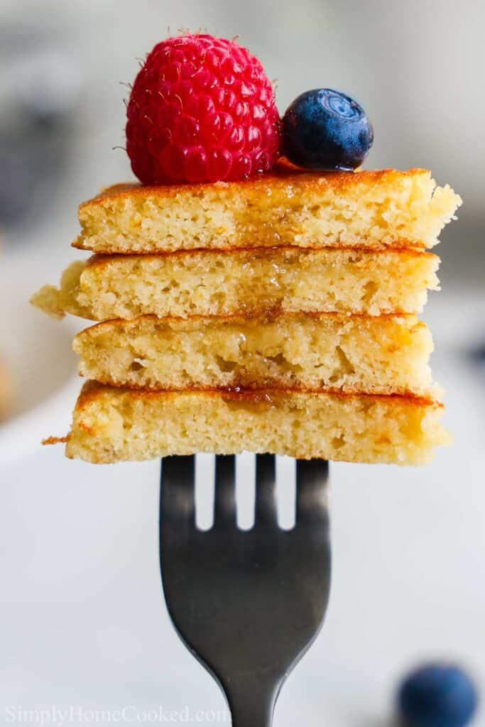 Forkful of Almond Flour Pancakes with a raspberry and blueberry on top.