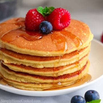 close up image of a stack of almond flour pancakes on a white plate with berries and syrup on top