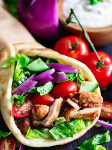 Chicken Shawarma in a pita with vegetables and yogurt sauce nearby
