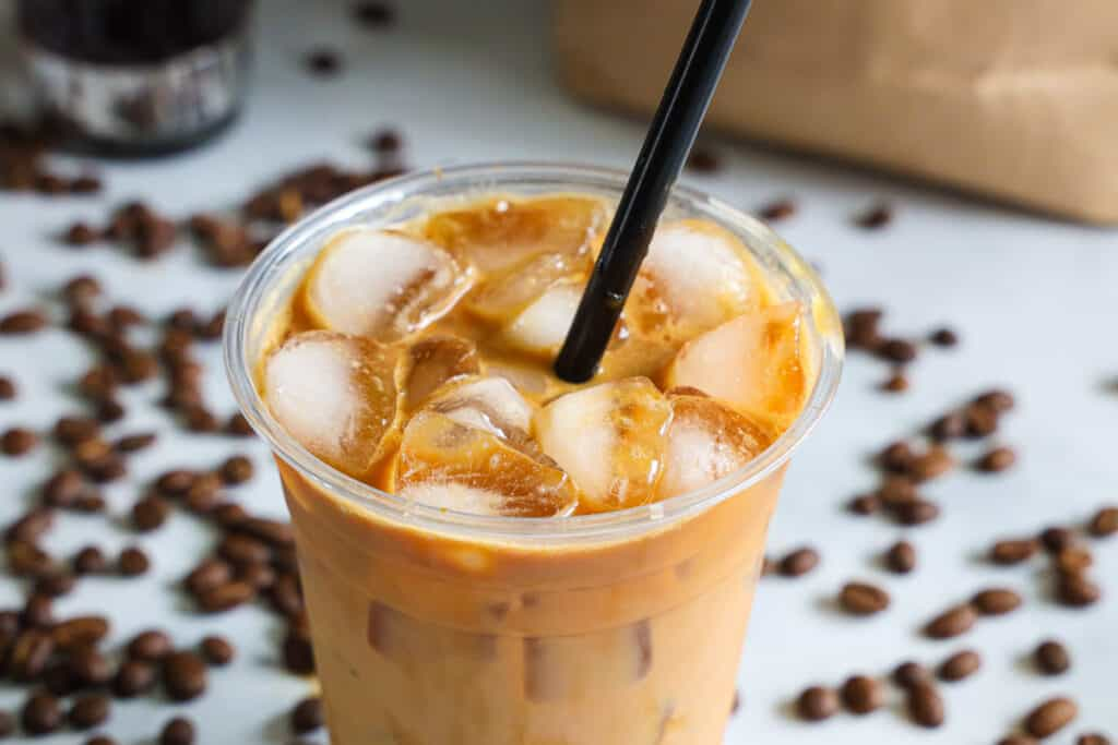 horizontal image of iced caramel macchiato with ice at the top of the cup