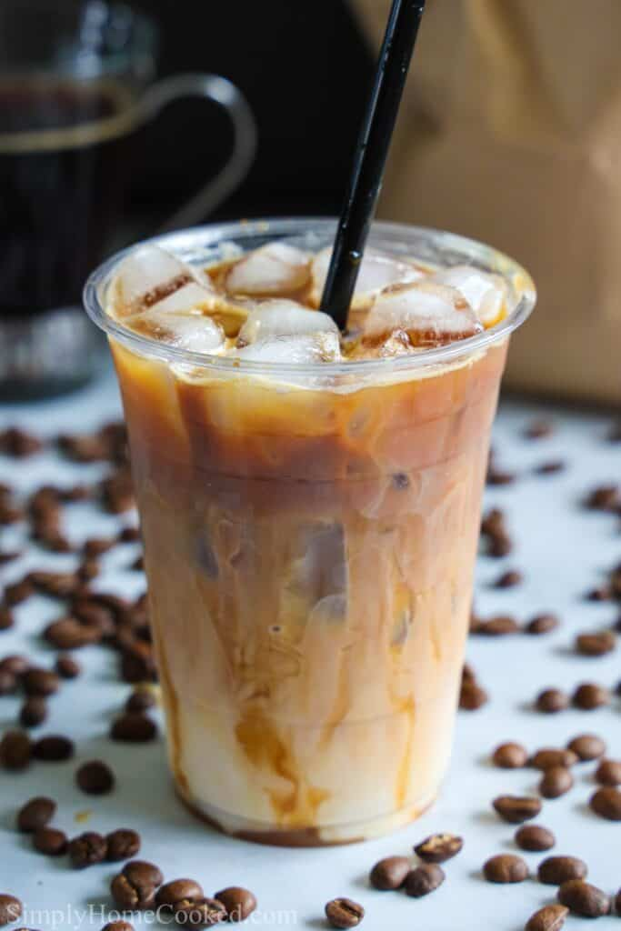 close up image of homemade iced caramel macchiato in a plastic cup with a black straw inside and coffee beans scattered around