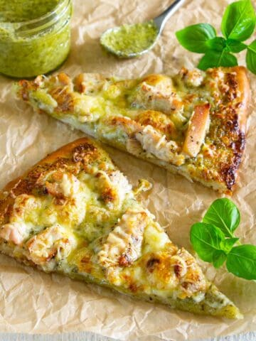 Slices of Chicken Pesto Pizza with pesto and basil nearby