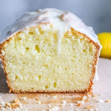 low angle image of a lemon pound cake on a wooden cutting board that has one side sliced off