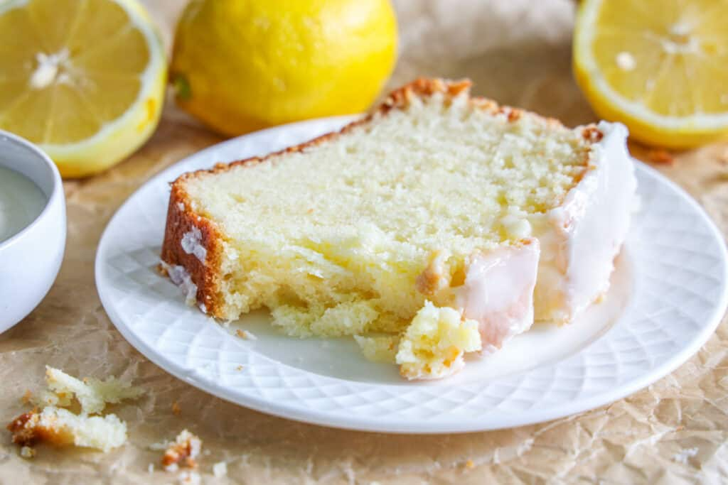 close up image of a slice of lemon loaf on a white plate with lemons in the background