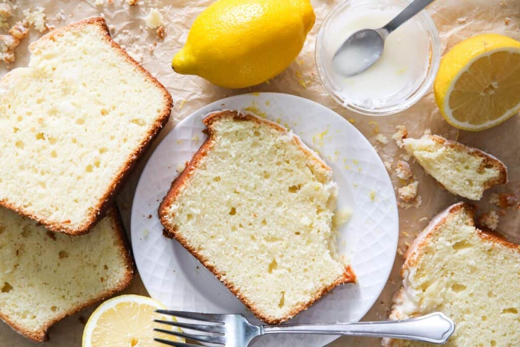 overhead image of a slice of lemon pound cake on a white plate with lemon and crumbs around it