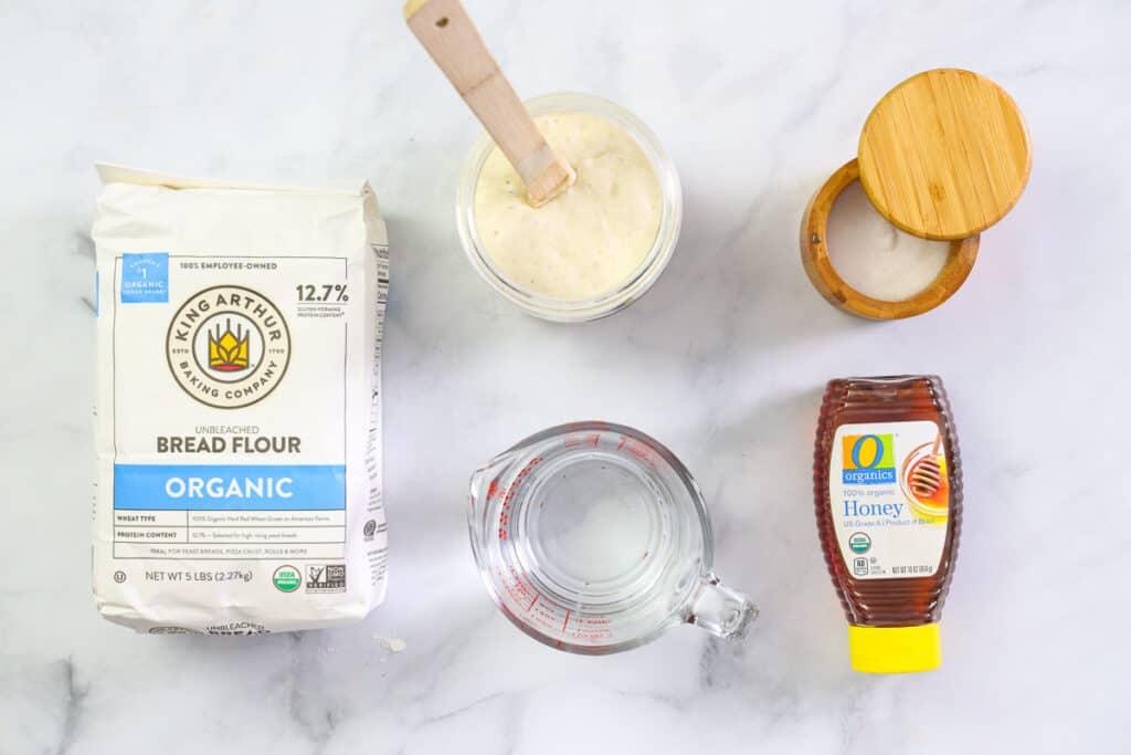 Ingredients for Sourdough Bagels, including sourdough starter, water, bread flour, honey, and salt.