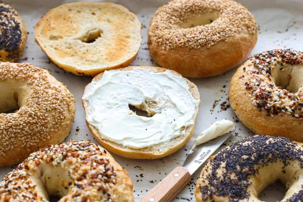 Sourdough bagels with different toppings, one spread with cream cheese, and a knife.