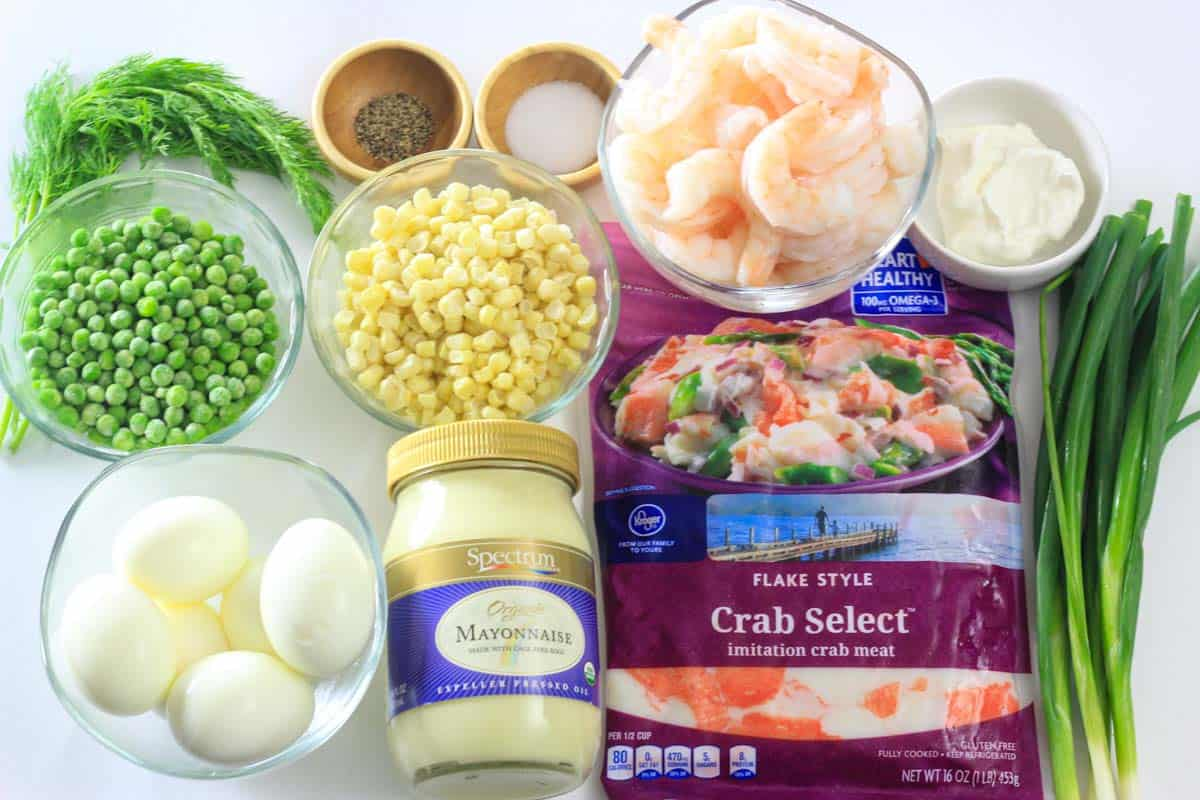 Ingredients for Crab Salad, including Imitation crab meat, Cooked shrimp, Green onions, Peas, White corn , Eggs, Sour cream, Mayonnaise, Dill, Salt, and Pepper.