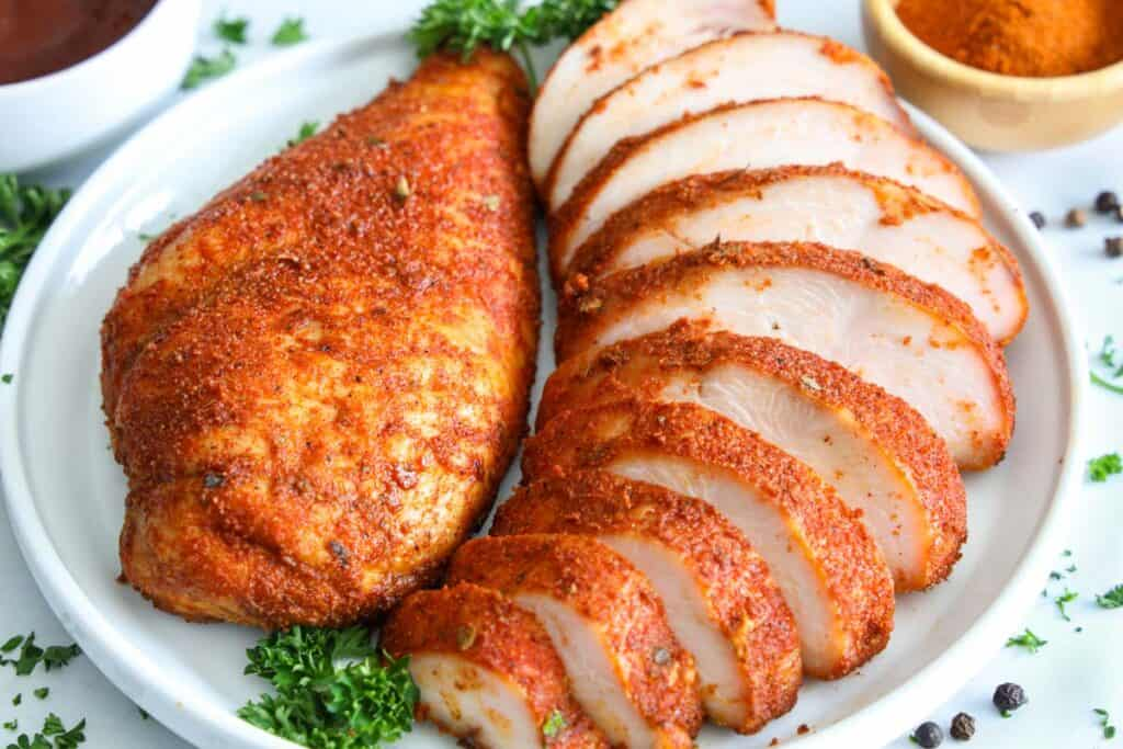 Horizontal image of Smoked Chicken Breast sliced on a plate with a parsley garnish